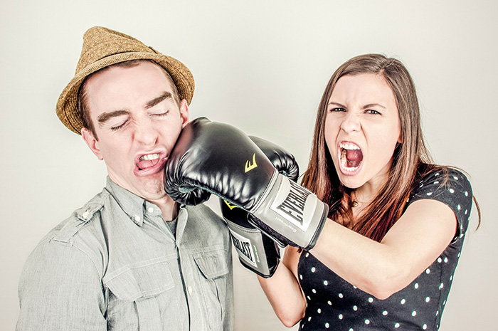 Female with boxing gloves on punching male wearing a hat on the cheek side of face