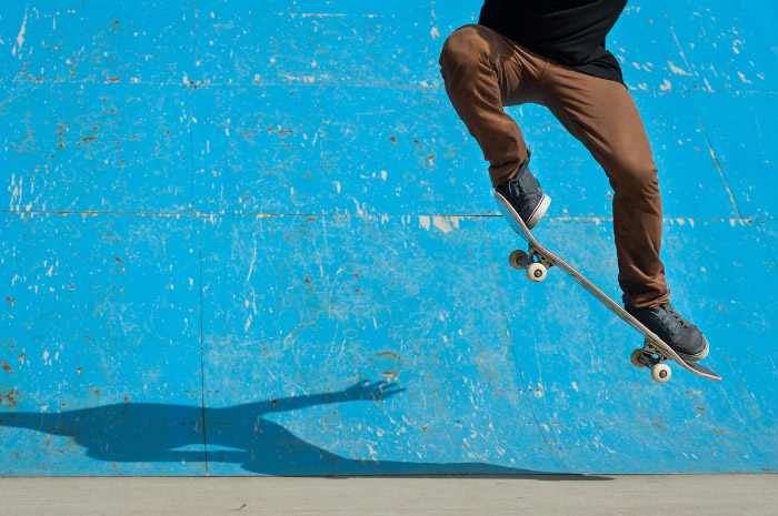 Man skateboarding in air with blue background wall