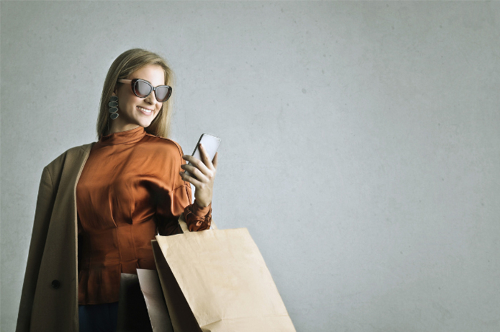 Female shopper wearing beautiful clothing and sunglasses with big smile looking at her phone holding a brown paper shopping bag