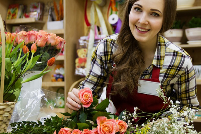 Business owner florist putting together a bunch of flowers smiling