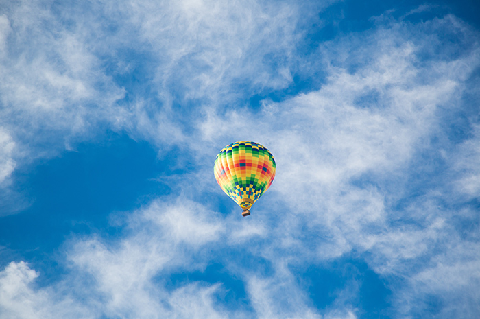 Hot air balloon up in the blue sky with white clouds