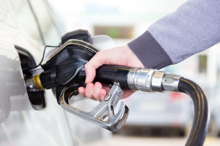Person holding fuel pump filling up motor vehicle with petrol