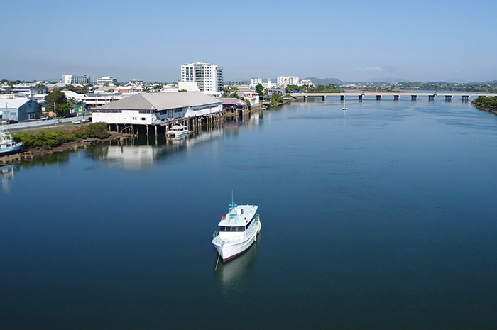 Cruise ship sailing along Pioneer River in Mackay with bridge in background