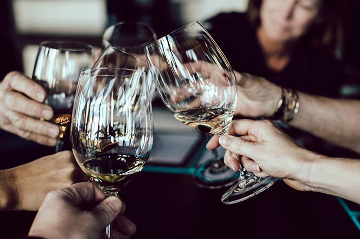 Group of people cheering wine glasses