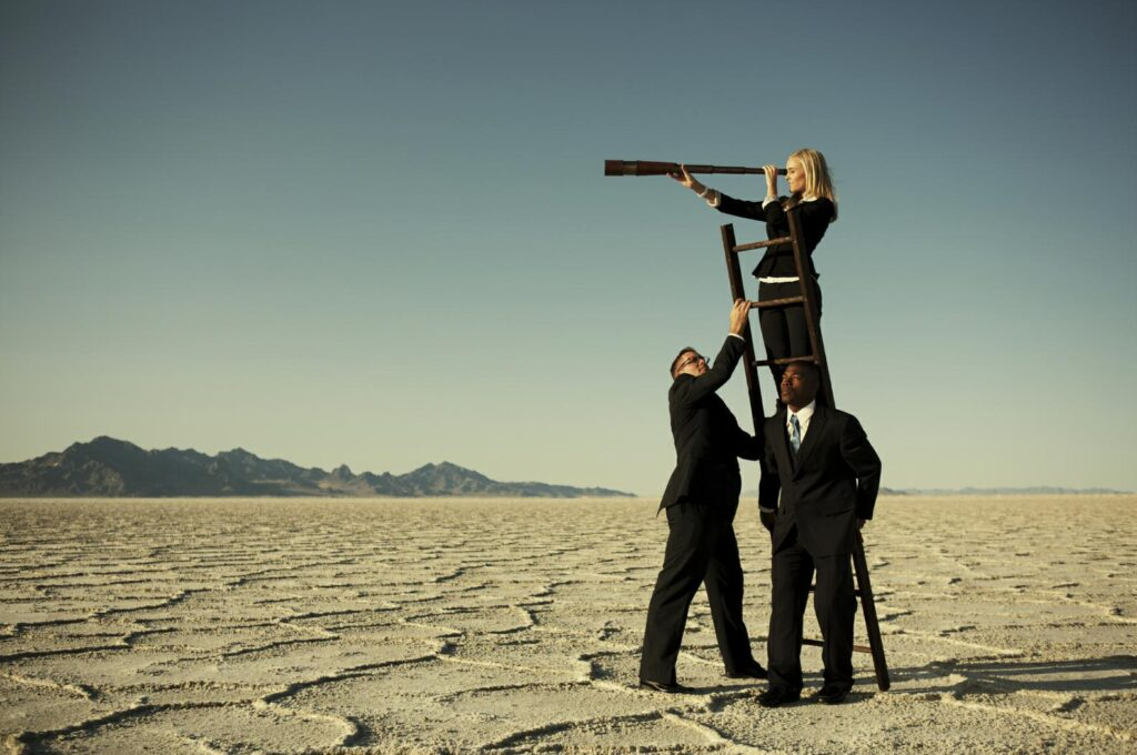 Two men in black business suits holding up a ladder with a business woman peering into a telescope at the top of the ladder