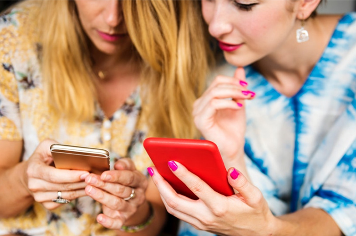Two women looking at phones in colourful dresses