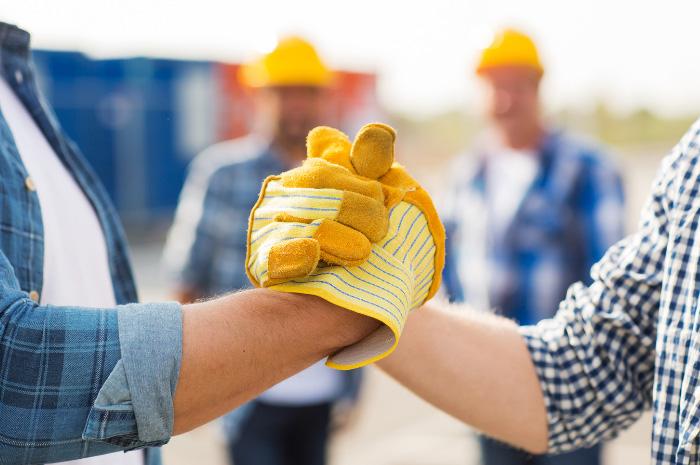 Tradesman and business man handshake on construction site