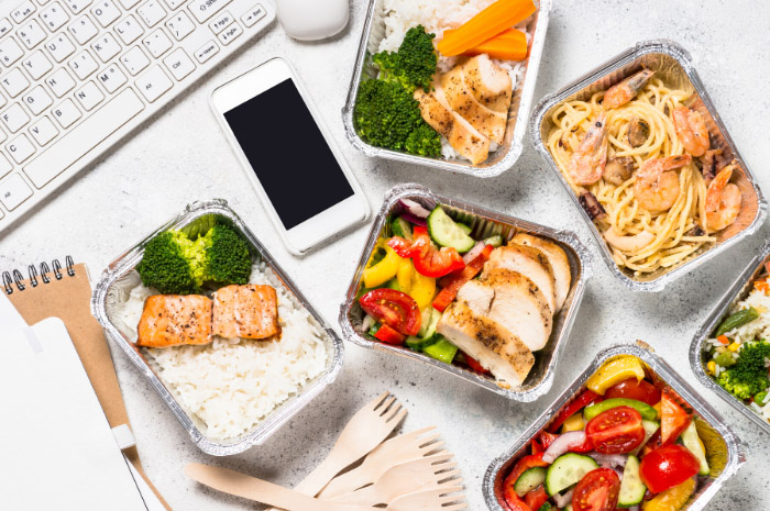 A variety on healthy food dishes on desk near computer keyboard and phone