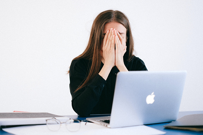 Woman sitting at desk in front of computer with head in her hands stressed