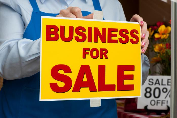 Florist holding up Business For Sale sign