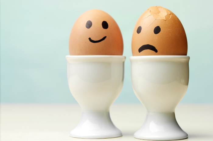 Two eggs in egg cups one with a happy face and the other with a sad face and slightly cracked shell