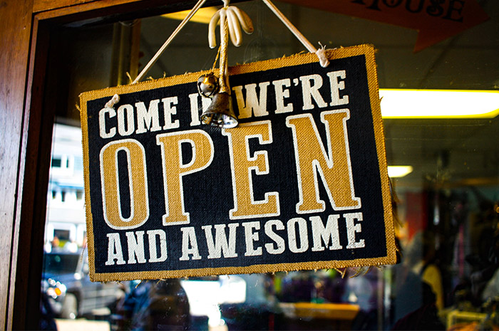 Open sign on shop door saying come in we are open and awesome