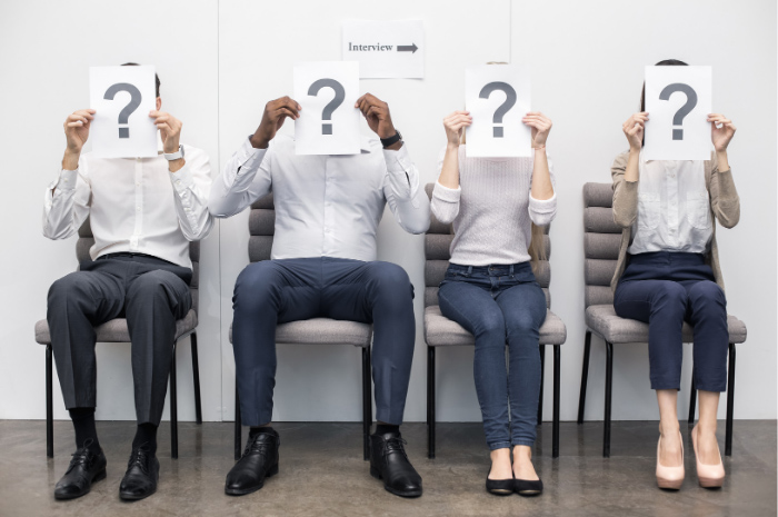 Four interviewees in waiting room with question mark over their faces