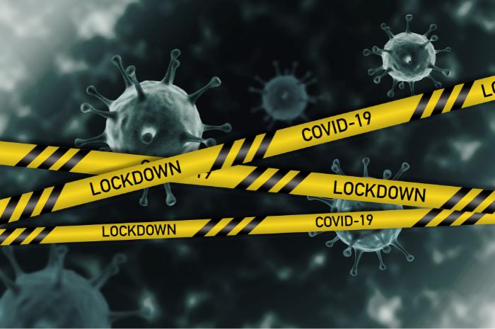 Coronavirus symbols floating around with yellow safety warning tape reading COVID-19 LOCKDOWN