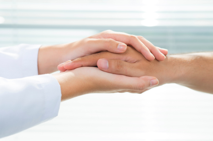 Two hands holding hand reached out for support