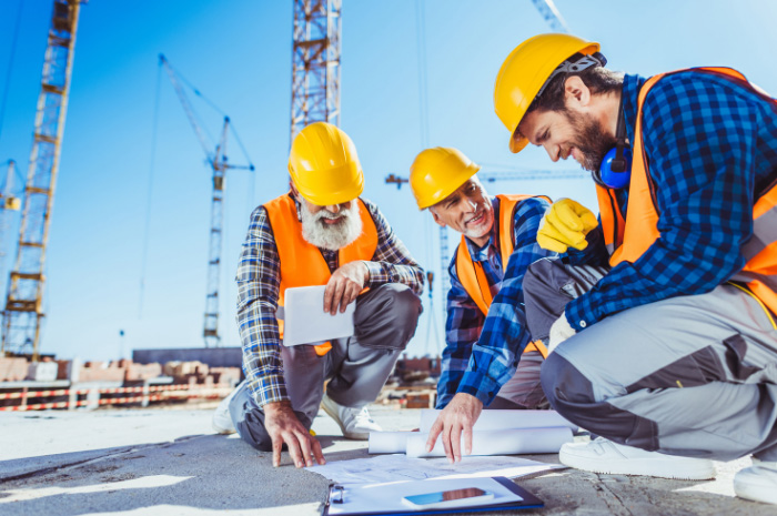 Tradesmen on concrete slab of construction site pointing to documents