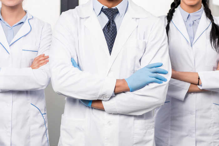 Doctors with arms folded in white protective attire