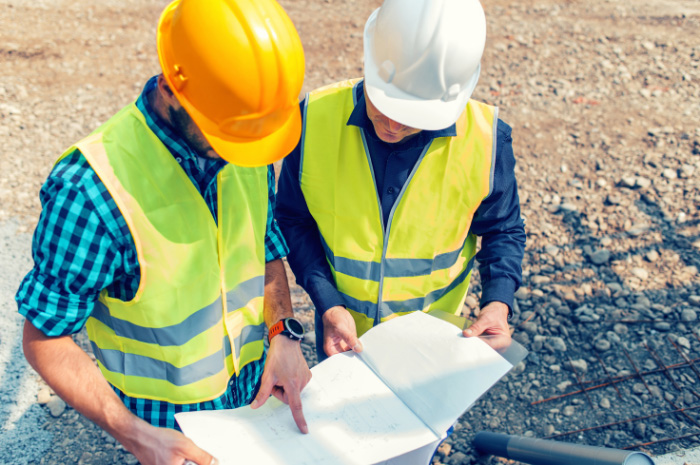 Tradesmen looking over plans on construction site