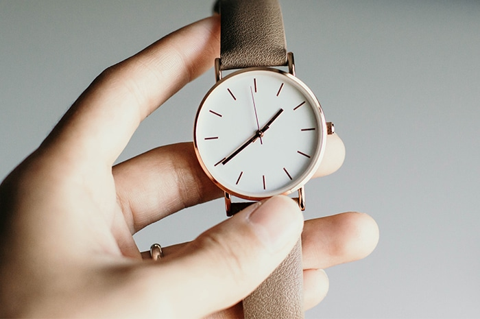 Hand holding watch with white face gold hardware and beige band