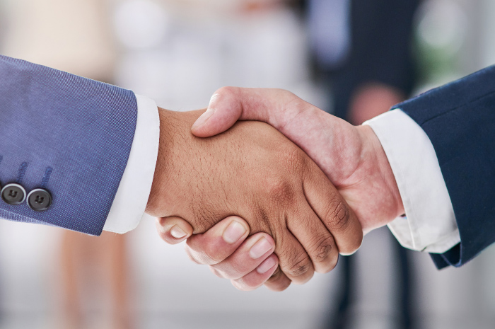 Men in corporate attire shaking hands on business deal