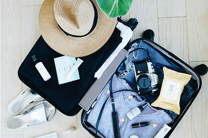 Suitcase open with camera clothing hat and shoes