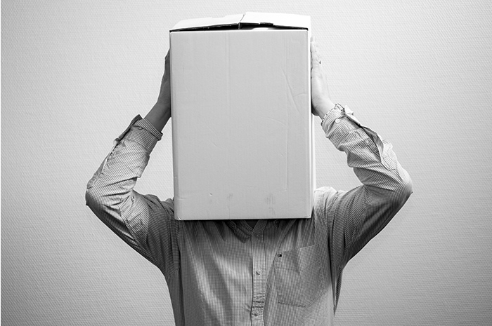 Man in corporate business shirt holding cardboard box over his head