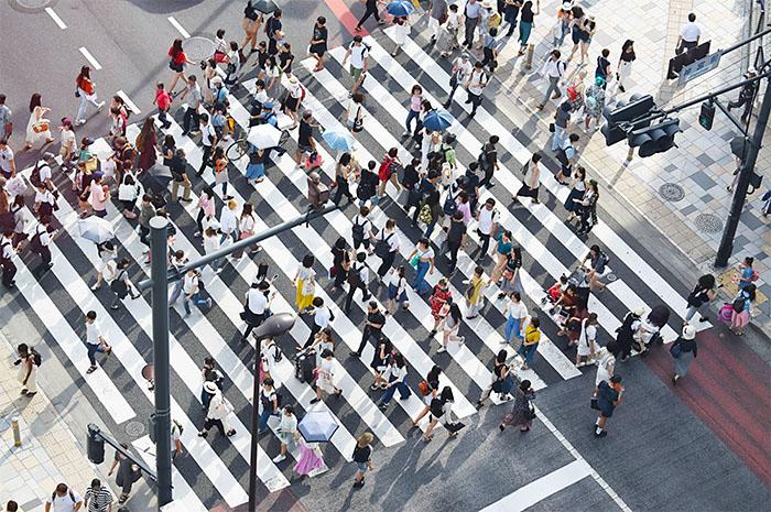 Crowd of people walking across wide pedestrian crossing past traffic lights