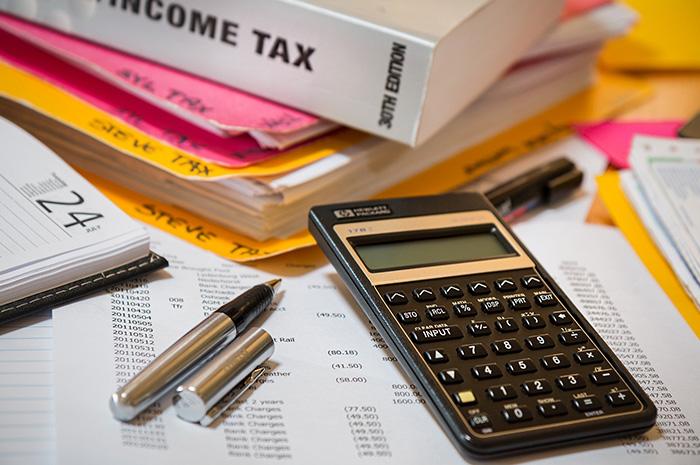 Tax folders diary pen calculator and files on desk