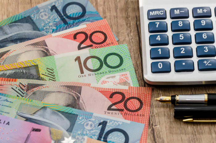 Australian currency notes on desk beside calculator and pens