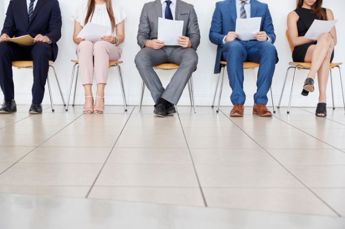 Row of seated people in corporate attire in interview waiting room