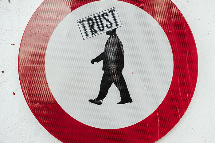Red circle with silhouette of man in centre and words TRUST