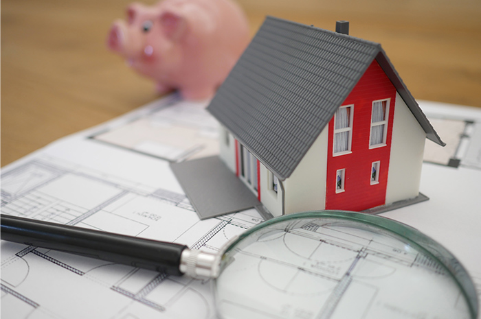 House plans with small house display piggy bank and magnifying glass