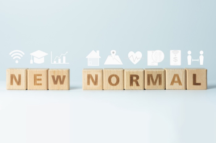 Wooden letter blocks spelling NEW NORMAL with pandemic related icons above in white
