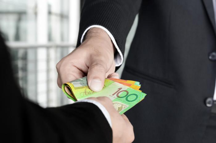 Men in business suits exchanging Australian dollars